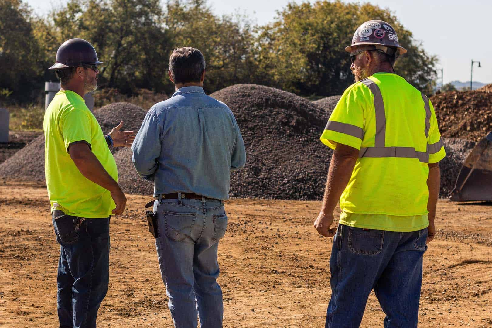 Three men looking at an excavation site