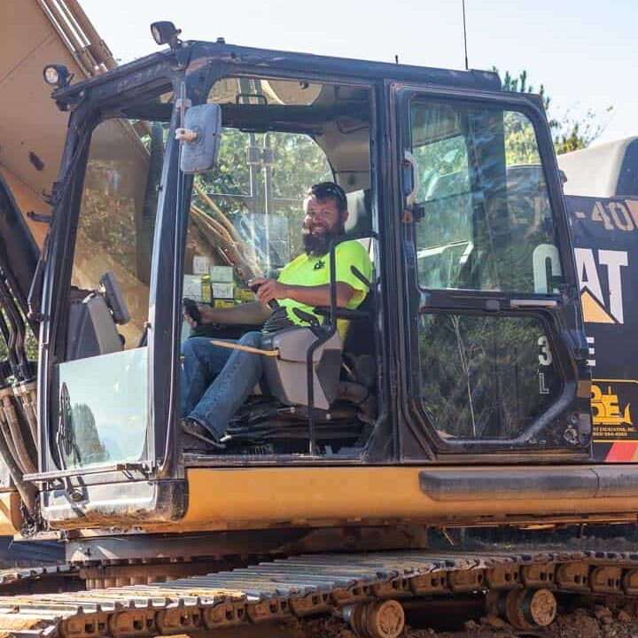 A man sitting in the cab of a piece of equipment smiling at the camera