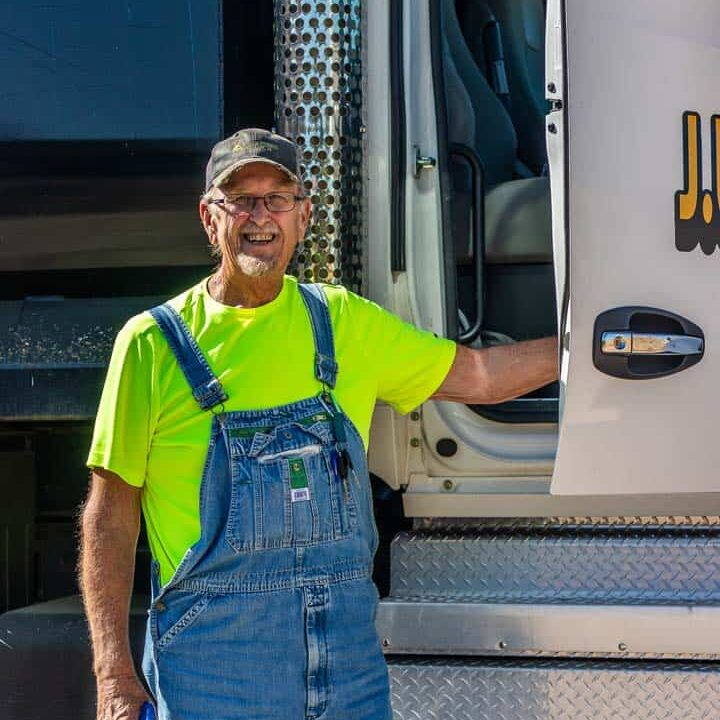 A man smiling while getting out of a dump truck